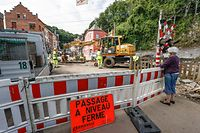 A woman watches workers at a level crossing of a partly-destroyed street following heavy floods in Dinant, central Belgium, on July 29, 2021. - In mid-July western Europe was hit by devastating floods after torrential rains that ravaged entire villages and left at least 209 people dead in Germany and Belgium, as well as dozens missing. The flooding also caused damage in Luxembourg, the Netherlands and Switzerland. (Photo by BRUNO FAHY / BELGA / AFP) / Belgium OUT