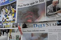 A woman passes in front of a newspaper stall, selling Lebanese newspapers featuring on their front pages images of the fire that ravaged the Parisian Notre Dame cathedral, in the capital Beirut on April 16, 2019. - Paris was struck in its very heart as flames devoured the roof of Notre-Dame, the medieval cathedral made famous by Victor Hugo, its two massive towers flanked with gargoyles instantly recognisable even by people who have never visited the city. (Photo by ANWAR AMRO / AFP)