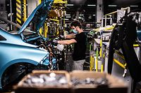 TOPSHOT - An employee wearing a protective mask against the spread of the novel coronavirus, COVID-19, works along the assembly line that produces both the electric vehicle Renault Zoe and the hybrid vehicle Nissan Micra, at Flins-sur-Seine, the largest Renault production site in France on May 6, 2020. - To reopen following the March 17th lockdown across France, the factory has had to enforce all the safety measure required to reduce any spread of COVID-19 at the assembly plant, with workers having to wear protective masks and gloves and diving the assembly line into individual parts to spot any person-to-person contamination. (Photo by Martin BUREAU / AFP)