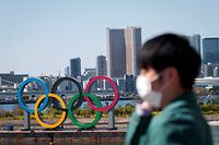 A man wearing a face mask, amid concerns over the spread of the COVID-19 novel coronavirus, stands before the Olympic rings from an observation point in Tokyo's Odaiba district on March 25, 2020, the day after the historic decision to postpone the 2020 Tokyo Olympic Games. - Japan on March 25 started the unprecedented task of reorganising the Tokyo Olympics after the historic decision to postpone the world's biggest sporting event due to the COVID-19 coronavirus pandemic that has locked down one third of the planet. (Photo by Behrouz MEHRI / AFP)