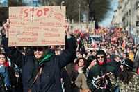 A man holds a banner calling for the stopping of wars, environmental pollution and other current issues, as thousands of people take part in a demonstration in Nantes, western France, on January 16, 2020, as part of a nationwide multi-sector strike against the French government's pensions overhaul. - Unions have been waging a transport strike against the pension overhaul since December 5, 2019, the longest transport strike in France in decades. (Photo by Loic VENANCE / AFP)