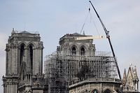 "Fire fighters are at work on top of a tower of Notre-Dame Cathedral, as a crane lifts up constreuction material in Paris on April 17, 2019, two days after a fire that devastated the building in the centre of the French capital. - French President vowed on April 16 to rebuild Notre-Dame cathedral ""within five years"", after a fire which caused major damage to the 850-year-old Paris landmark. (Photo by Thomas SAMSON / AFP)"