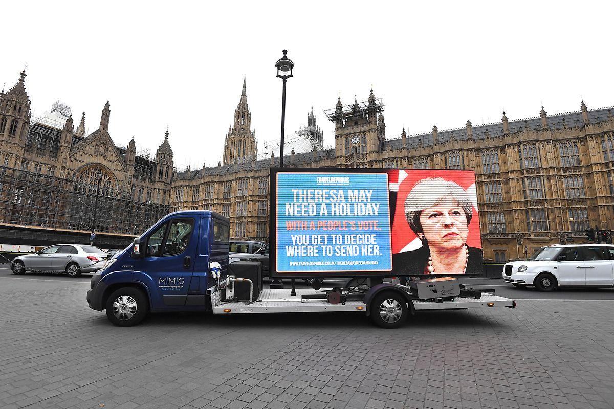 """Auf einem Bildschirm auf dem Anhänger eines LKWs steht """"Theresa May needs a holiday. With a people's vote, you get to decide where to send her."""" (Theresa May braucht Urlaub. Mit einer Volksabstimmung entscheidest du, wohin sie geschickt wird.) vor den Parlamentsgebäuden in Westminster."""