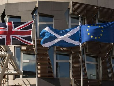 A Scottish Saltire (C) flies between a Union flag (L) and a European Union (EU) flag in front of the Scottish Parliament building in Edinburgh, Scotland on June 27, 2016. British leaders battled to calm markets and the country Monday after its shock vote to leave the EU, while insisting London would be not rushed into a quick divorce. Britain's historic decision to be the first country to leave the 28-nation bloc has fuelled fears of a break-up of the United Kingdom with Scotland eyeing a new independence poll, and created turmoil in the opposition Labour party where leader Jeremy Corbyn is battling an all-out revolt. / AFP PHOTO / OLI SCARFF