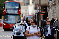 Commuters, some wearing face coverings due to Covid-19, walk outside Victoria Station in central London on June 7, 2021. - The Delta variant of the coronavirus, first discovered in India, is estimated to be 40 percent more transmissible than the Alpha variant that caused the last wave of infections in the UK, Britain's health minister said Sunday. (Photo by Tolga Akmen / AFP)