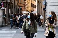 Women walk in downtown Rome, on October 25, 2020, as the country faces a second wave of infections to the Covid-19 (the novel coronavirus). - Italy's Prime Minister Giuseppe Conte tightened nationwide coronavirus restrictions on October 25, 2020 after the country registered a record number of new cases, despite opposition from regional heads and street protests over curfews. Cinemas, theatres, gyms and swimming pools must all close under the new rules, which come into force on October 26, 2020 and run until November 24, while restaurants and bars will stop serving at 6pm, the prime minister's office said. (Photo by Vincenzo PINTO / AFP)