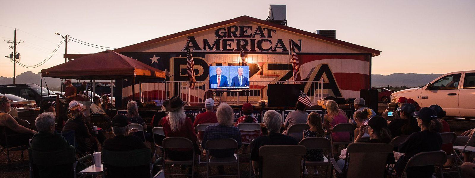 Anhänger von US-Präsident Donald Trump verfolgen die zweite TV-Debatte vor einem Pizza-Restaurant in Arizona.