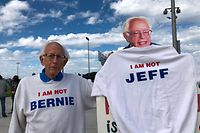 """Jeff Jones, 77, wearing his """"I am not Bernie Sanders"""" sweater, poses next a Bernie Sanders cutout at a Sanders rally at a Santa Ana, California, high school on February 21, 2020. - Up until a few years ago, Jeff Jones was going about his life, minding his own business and enjoying his passion for music. Then Bernie Sanders burst onto the national political stage, prompting many to do double takes on seeing Jones, who bears a striking resemblance to the Democratic presidential candidate. (Photo by Javier TOVAR / AFP)"""