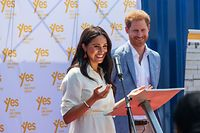 (FILES) In this file photo taken on October 2, 2019 Meghan, Duchess of Sussex (L), is watched by Britain's Prince Harry, Duke of Sussex (R) as she delivers a speech at the Youth Employment Services Hub in Tembisa township, Johannesburg. - Britain's Prince Harry and his wife Meghan handed out meals to sick people in Los Angeles, in their first known public activity since moving to California at the start of the state's coronavirus lockdown. The pair, who have formally stepped down as senior members of the British royal family, first volunteered with Project Angel Food last on April 12, 2020, delivering food to homes. (Photo by Michele Spatari / AFP)