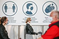 Travellers wearing a protective face mask, walk past infomation signs indicating the sanitary measures and rules at Brussels Airport, in Zaventem, on June 15, 2020 as Brussels Airport reopens for travels within Europe and the Schengen zone, after a months-long closure aimed at stemming the spread of the COVID-19 pandemic, caused by the novel coronavirus. (Photo by BRUNO FAHY / Belga / AFP) / Belgium OUT