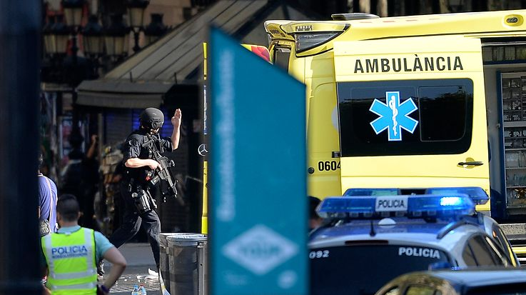 """TOPSHOT - An armed policeman arrives in a cordoned off area after a van ploughed into the crowd, injuring several persons on the Rambla in Barcelona on August 17, 2017. Police in Barcelona said they were dealing with a """"terrorist attack"""" after a vehicle ploughed into a crowd of pedestrians on the city's famous Las Ramblas boulevard on August 17, 2017. Police were clearing the area after the incident, which has left a number of people injured. / AFP PHOTO / Josep LAGO"""