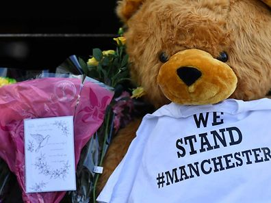 Flowers, a teddy bear, and messages of support are pictured outside Victoria Station car park, near to the Manchester Arena