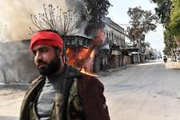 TOPSHOT - A Turkish-backed Syrian rebel walks past a burning shop in the city of Afrin in northern Syria on March 18, 2018. Turkish forces and their rebel allies were in control of the Kurdish-majority city of Afrin in northwestern Syria, AFP journalists on the ground reported.  / AFP PHOTO / BULENT KILIC