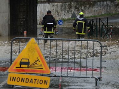 A fireman crosses a flooded road with a person on his back following heavy rainfalls on May 31, 2016 in Meung-sur-Loire southern Orleans, as the Loiret department is under flood alert and France's weather agency Meteo France maintained 18 departments under orange alert.    / AFP PHOTO / GUILLAUME SOUVANT