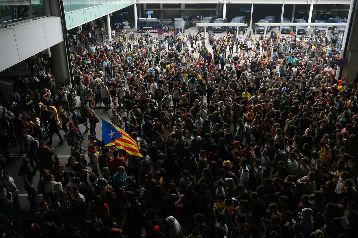 "TOPSHOT - A protester holds a Catalan pro-independence ""Estelada"" flag surrounded by other protesters at El Prat airport in Barcelona on October 14, 2019 as thousands took to the streets after Spain's Supreme Court sentenced nine Catalan separatist leaders to between nine and 13 years in jail for sedition over the failed 2017 independence bid. - As the news broke, demonstrators turned out en masse, blocking streets in Barcelona and elsewhere as police braced for what activists said would be a mass response of civil disobedience. (Photo by LLUIS GENE / AFP)"