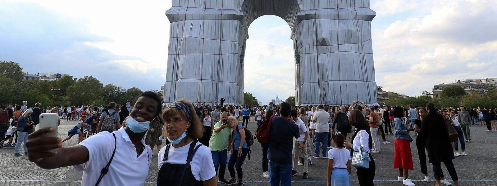Spaziergänger machen am Samstag Selfies vor dem verhüllten Triumphbogen in Paris.