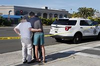 People hug next to police tape across the street from the Chabad of Poway Synagogue after a shooting on April 27, 2019 in Poway, California. - A gunman opened fire at a synagogue in California, killing one person and injuring three others including the rabbi as worshippers marked the final day of Passover, officials said Saturday, April 27, 2019. The shooting in the town of Poway came exactly six months after a white supremacist shot dead 11 people at Pittsburgh's Tree of Life synagogue -- the deadliest attack on the Jewish community in the history of the United States. (Photo by SANDY HUFFAKER / AFP)