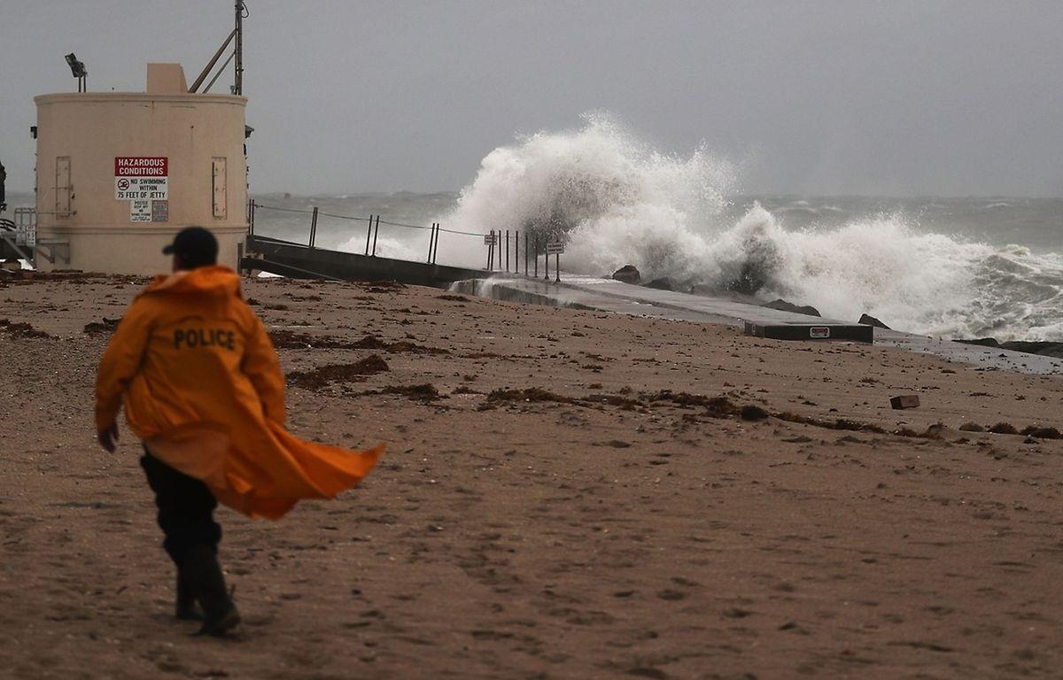Ein Polizist überwacht einen Strand in Florida. Besonders die küstennahen Gebiete sind von dem Sturm bedroht.