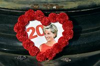 This picture shows a photograph of Princess Diana circled by flowers on August 29, 2017, in Paris, around the Flame of Liberty statue plastered with iconic photos, flowers and messages, two days prior to the 20th anniversary of her death. The Flame of Liberty statue became the Paris� unofficial memorial to Ladi Di, near the Pont de l�Alma tunnel where she died in a car crash on August 31, 1997. / AFP PHOTO / ALAIN JOCARD