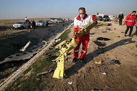 TOPSHOT - EDITORS NOTE: Graphic content / Rescue teams recover debris from a field after a Ukrainian plane carrying 176 passengers crashed near Imam Khomeini airport in the Iranian capital Tehran early in the morning on January 8, 2020, killing everyone on board. - The Boeing 737 had left Tehran's international airport bound for Kiev, semi-official news agency ISNA said, adding that 10 ambulances were sent to the crash site. (Photo by - / AFP)