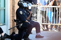 "TOPSHOT - San Francisco police officers kneel after a crowd of protesters called for them to ""take a knee"" in front of a police station in San Francisco, California on June 3, 2020. - Thousands of people gathered at Dolores Park and marched through the city in support of George Floyd and against police brutality. (Photo by Josh Edelson / AFP)"