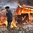 """A migrant walks past shacks burning during the dismantling of half of the """"Jungle"""" migrant camp in the French northern port city of Calais, on February 29, 2016. Clashes broke out between French riot police and migrants on February 29 as bulldozers moved into the grim shantytown on the edge of Calais known as the """"Jungle"""" to start destroying hundreds of makeshift shelters. AFP PHOTO / PHILIPPE HUGUEN"""