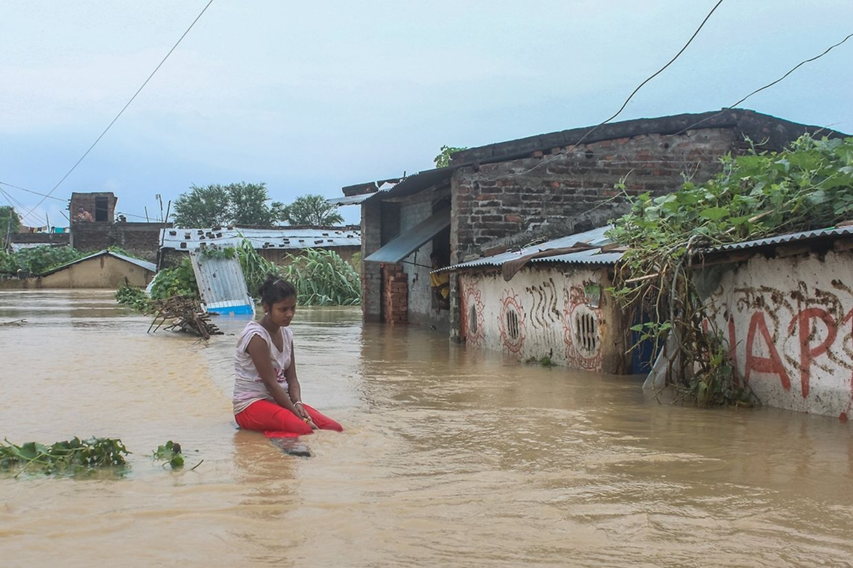 A woman sits outside her house floded due to Sirisiya River in Ramghaduwa , Parsa District , Nepal