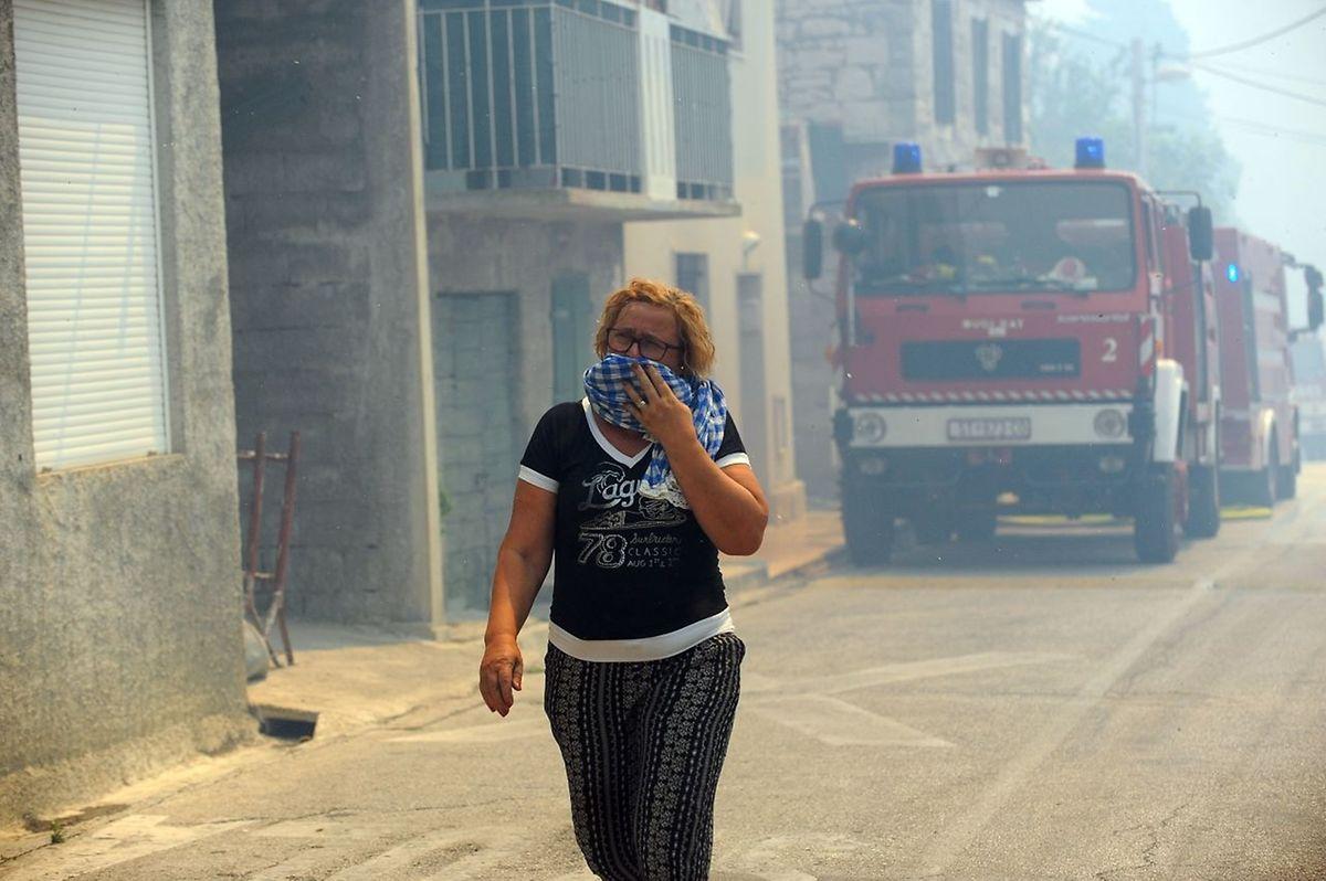 In einem Vorort der Küstenstadt Split schützt sich eine Frau vor dem Rauch.