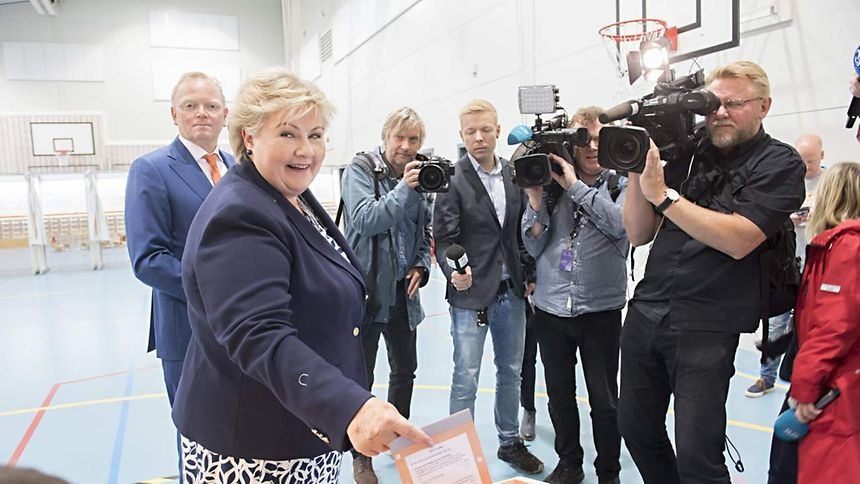 Norway`s Prime Minister Erna Solberg cast her ballot flanked by her husband Sindre Finnes (L) at a polling station in Bergen during general election on September 11, 2017.
