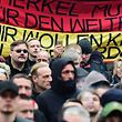 Participants of a demonstration by far-right groups hold up banners calling for Merkel to go on account of her refugee policies in Berlin on March 12, 2016. / AFP PHOTO / John MACDOUGALL