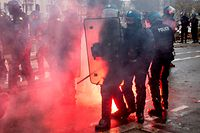 "TOPSHOT - Riot police members walk forward carrefully past a flare lying on the ground during a protest of ""yellow vests"" (gilets jaunes) against rising costs of living they blame on high taxes in Nantes, eastern France on December 8, 2018. - French ""yellow vest"" demonstrators clashed with riot police in Paris on December 8, 2018 in the latest round of protests against President Emmanuel Macron, but the city appeared to be escaping the large-scale destruction of a week earlier due to heavy security. (Photo by Sebastien SALOM-GOMIS / AFP)"