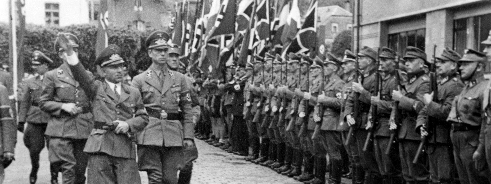Gustav Simon - hier bei einem Aufmarsch von NS-Truppen -  entzieht sich nach Ende des Krieges der Verantwortung und begeht Selbstmord.