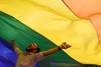 "TOPSHOT - A member of the lesbian, gay, bisexual, transgender (LGBT) community celebrates the Supreme Court decision to strike down a colonial-era ban on gay sex, in Mumbai on September 6, 2018. - India's Supreme Court on September 6 struck down the ban that has been at the centre of years of legal battles. ""The law had become a weapon for harassment for the LGBT community,"" Chief Justice Dipak Misra said as he announced the landmark verdict. (Photo by INDRANIL MUKHERJEE / AFP)"