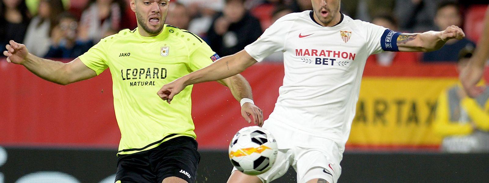 Sergio Escudero (de branco e capitão do Sevilha) em luta com Corenthyn Lavie (de amarelo), jogador do Dudelange.