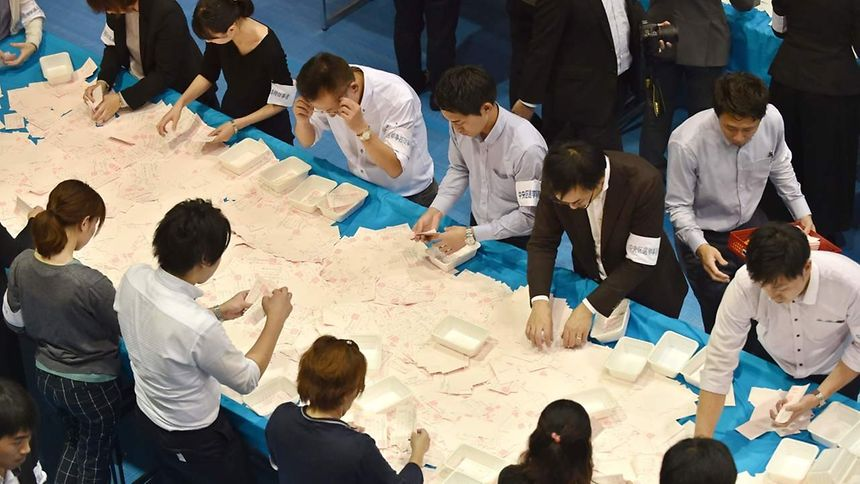 Officials of the election administration committee count ballot papers for Japan's general election