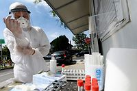 A medical worker wearing protective equipment puts on gloves at a drive-through COVID-19 test centre on August 27, 2020, in Zagreb. - Croatia recorded its highest number of daily coronavirus infections on August 26 as a tricky summer tourism season brings a resurgence of COVID-19 to the Adriatic country. The nation of 4.2 million braved the first few months of the pandemic without strict lockdown measures, recording less than 100 cases daily for several months and then almost no new infections by mid-May. But new cases have spiked since Croatia opened its borders to tourists for the summer season, hitting more than 200 daily in late August and a record 358 on August 26. (Photo by DENIS LOVROVIC / AFP)