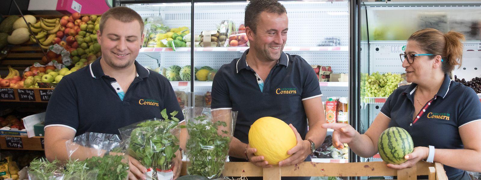 Daniel Abrantes Boto (Mitte) bietet in seinem Dorfladen täglich frisches Obst und Gemüse an. Seine zwei Mitarbeiter, Alex und Fatima, helfen beim Einräumen.