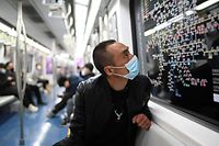 A man wearing a face mask, amid concerns of the COVID-19 coronavirus, looks at a subway map on a train in Beijing on April 3, 2020. (Photo by WANG ZHAO / AFP)