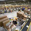 Sitz in Luxemburg, Kunden in ganz Europa: Mitarbeiter bereiten beim Onlinehändler Amazon Artikel für den Versand vor.