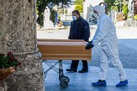 An undertaker wearing a face mask and overalls unloads a coffin out of a hearse on March 16, 2020 at the Monumental cemetery of Bergamo, Lombardy, as burials of people who died of the new coronavirus are being conducted at the rythm of one every half hour. (Photo by Piero Cruciatti / AFP)
