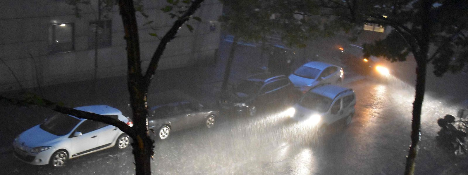 A person drives a vehicle under a heavy rainfall on July 9, 2017 in the 20th district of Paris.  Paris subway authorities closed metro stations due to flooding after thunderstorms and heavy rain pounded the French capital, officials said on July 10, 2017.  A violent two-hour storm struck the city late Sunday, forcing the closure of about 15 stations due to flooding, although they reopened Monday morning and traffic was normal, the Paris transport authority, the RATP, said. / AFP PHOTO / Christophe DELATTRE
