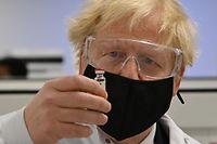 ARCHIV - 30.11.2020, Großbritannien, Wrexham: Boris Johnson, Premierminister von Großbritannien, hält ein Fläschchen des potenziellen Corona-Impfstoffs von Oxford/AstraZeneca, bekannt als AZD1222, in der Hand. (zu dpa «Nächste Woche schon 800 000 Corona-Impfstoffdosen in Großbritannien») Foto: Paul Ellis/PA Wire/dpa +++ dpa-Bildfunk +++