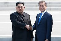 North Korea's leader Kim Jong Un (L) and South Korea's President Moon Jae-in shake hands at the Military Demarcation Line that divides their countries at Panmunjom on April 27, 2018. The two men briefly stepped back over the line into the North before walking to the Peace House building on the southern side of the truce village of Panmunjom for the summit -- only the third of its kind since hostilities ceased in 1953. / AFP PHOTO / Korea Summit Press Pool / Korea Summit Press Pool