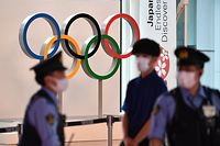 The Olympic rings are seen past policemen (L and R) at the arrival hall of the Tokyo International Airport in Tokyo on July 8, 2021, as International Olympic Committee President Thomas Bach landed in Japan for a visit. (Photo by Kazuhiro NOGI / AFP)