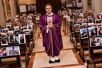 "TOPSHOT - Don Giuseppe Corbari, parson of the Church of Robbiano, poses between selfie photographs sent in by his congregation members and  glued to empty pews, before celebrating Sunday mass in Giussano on March 22, 2020. - Italian Prime Minister Giuseppe Conte on March 21 ordered all non-essential companies and factories to close nationwide to stem a coronavirus pandemic that has killed 4,825 people in the country in a month. ""The decision taken by the government is to close down all productive activity throughout the territory that is not strictly necessary, crucial, indispensable, to guarantee us essential goods and services,"" Conte said in a late-night TV address (Photo by Piero CRUCIATTI / AFP)"