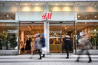 Shoppers walk past a fashion store of H&M (H & M Hennes & Mauritz AB) in central Stockholm on April 2, 2020. - Swedish retailer H&M said that the company have started dialogue with tens of thousands of staff about cutting working hours due to the coronavirus (Covid-19) pandemic effect on the market. (Photo by Fredrik SANDBERG / various sources / AFP) / Sweden OUT