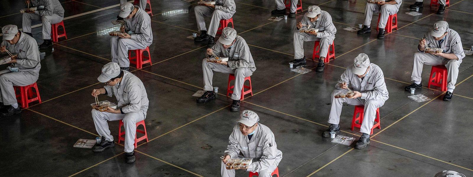 Arbeiter einer Autofabrik in Wuhan halten während des Mittagessens den notwendigen Sicherheitsabstand. Das Corona-Virus wird China noch länger begleiten.