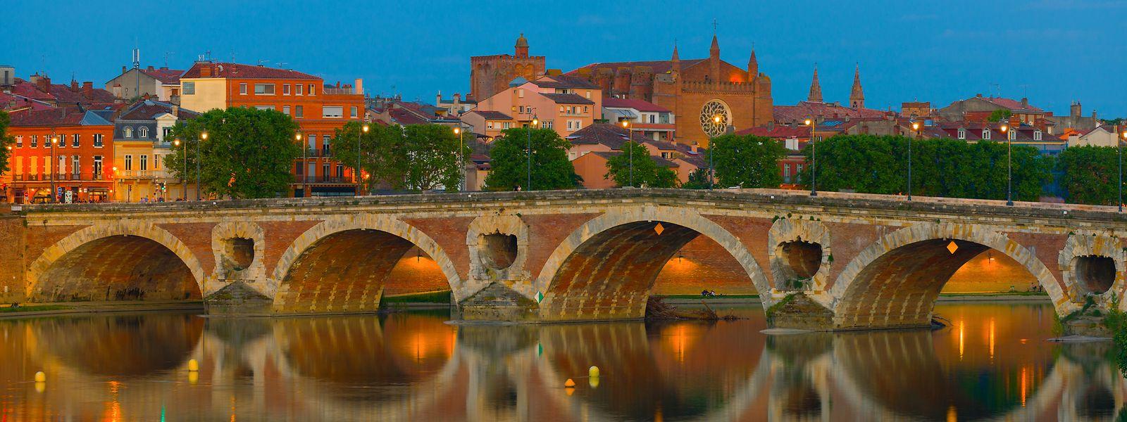 Zwei Symbolfarben auf einmal: Der rosarote Pont Neuf spiegelt sich bei blauem Himmel in der Garonne.