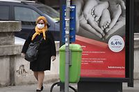 A woman with a face mask, worn by many people during the new coronavirus COVID-19 pandemic, walks past a bus station on March 26, 2020 in Budapest. - A woman with a face mask walks past a bus station on March 26, 2020 in Budapest. (Photo by ATTILA KISBENEDEK / AFP)
