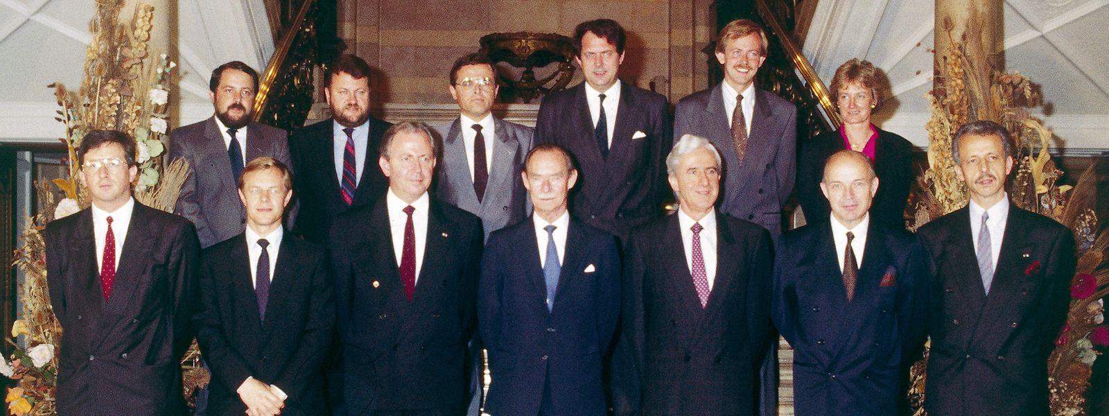 Die Regierung Santer-Poos II bei der Vereidigung am 14. Juli 1989: V.l.n.r. 1 R.: Jean-Claude Juncker, Fernand Boden, Jacques Santer, Großherzog Jean, Jacques Poos, Jean Spautz, Marc Fischbach; 2. R.: Georges Wohlfart, Robert Goebbels, Johny Lahure, René Steichen, Alex Bodry, Mady Delvaux-Stehres.